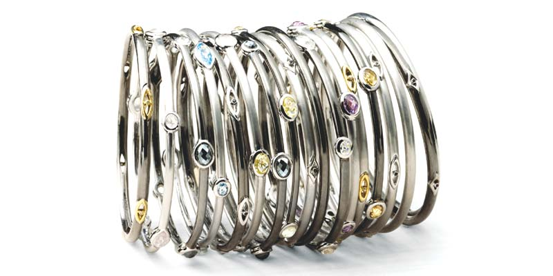 Assorted silver 'Cocktail Stax' bangles by Hera Jewellery, with midnight finish and gemstones.