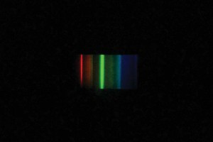 The three strong emission spikes of cool-white fluorescent tubes are clearly visible using a diffraction grating spectroscope and are the primary wavelengths produced.