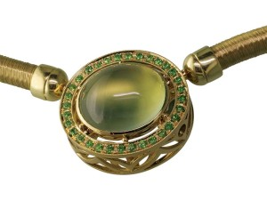 A green gold pendant featuring a bezel-set prehnite with demantoid garnets.