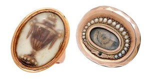 At left is a 19th-century memorial ring mounted in 14-karat gold. Its design features an urn composed of hair that is accented by seed pearls within  a glazed compartment. To the right is a 10-karat gold snake motif memorial brooch centring a coiled lock of hair within a glazed frame and surrounded by a split-pearl ouroboros.