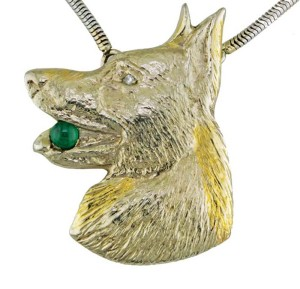 A client's wish for reliquary jewellery resulted in this pendant, which holds her son's cremains. The German Shepherd symbolizes his bond with his dog. The emerald is the son's birthstone, while the diamond came from his father's wedding band.
