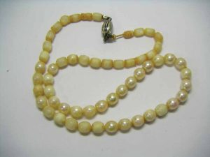 Only 21 out of the 56 barrel-shaped, 6- to 7-mm (0.23- to 0.27-in.) akoya cultured pearls in this necklace have not been damaged by acids originating from the human skin. The pearly layer has mostly been stripped away.