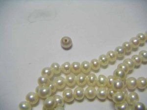 This single pearl, immersed in red wine for one hour, showed a distinct discolouration toward grey when compared to the string from which it was taken.