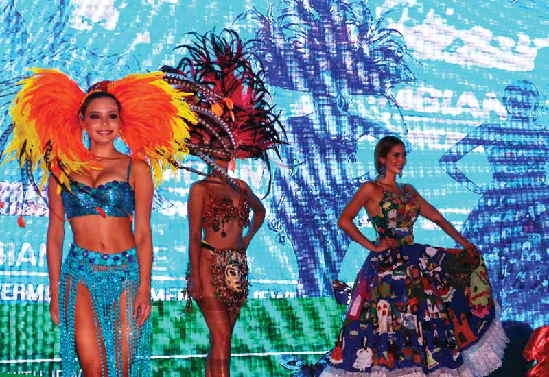 Models dressed in traditional Colombian attire wear emerald earrings during the gala dinner at the 2WES.