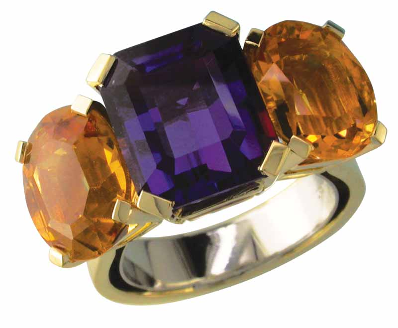 An 18-karat yellow gold ring with a white gold sizing spring inside, claw-set with large cushion-cut amethyst and two oval citrines.
