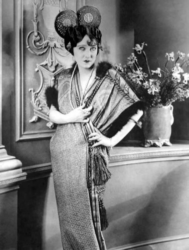 "Actress Gloria Swanson wearing a long beaded necklace in the 1919 film For Better, for Worse. <br /> <span style=""font-size: 10pt; font-family: arial, helvetica, sans-serif;""><i>Photo courtesy Wikimedia Commons</i></span>"