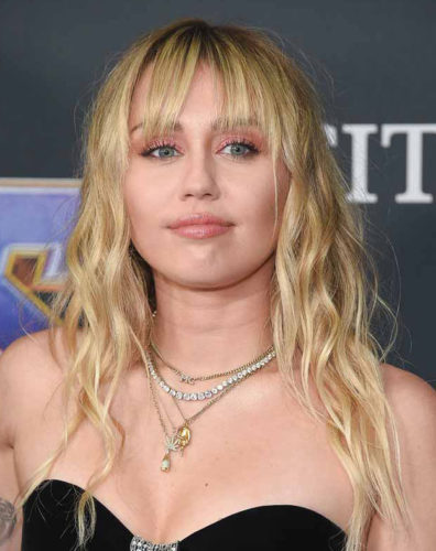 "Miley Cyrus wearing layered necklaces, one of which includes her initials, with a custom Saint Laurent gown  at the <i>Avengers: End Game premiere.</i><br /> <span style=""font-size: 10pt; font-family: arial, helvetica, sans-serif;"">"