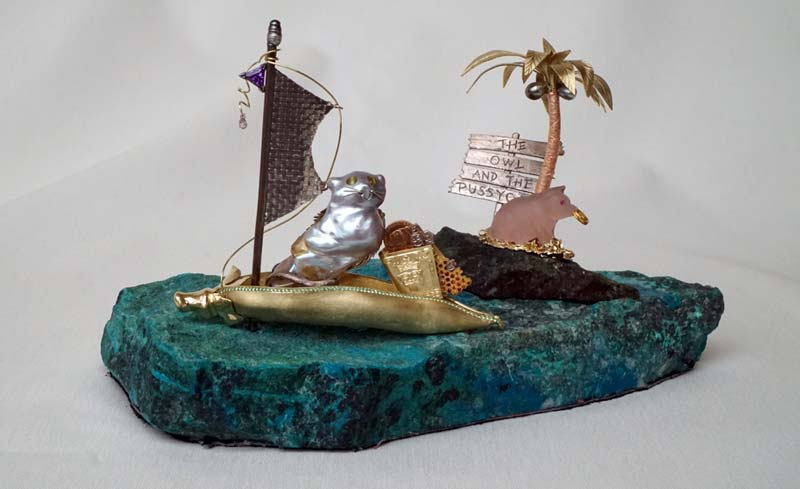 The characters are positioned aboard a green-gold peapod boat, accented with tsavorite garnets, a white gold mast topped with a black south sea keshi pearl, a tiny diamond briolette dew drop, and a sail of hand-woven platinum. The boat is 'afloat' on a two-pound piece of chrysocolla.