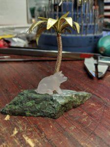 The carved rose-quartz pig on his island.