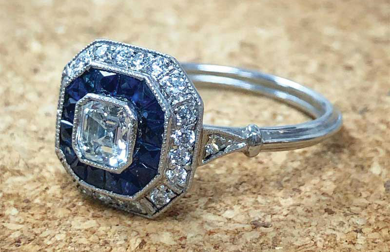 A handcrafted, platinum art deco-style diamond and sapphire halo engagement ring, featuring an Asscher-cut 0.50-carat diamond centre stone (I colour, VS2 clarity).