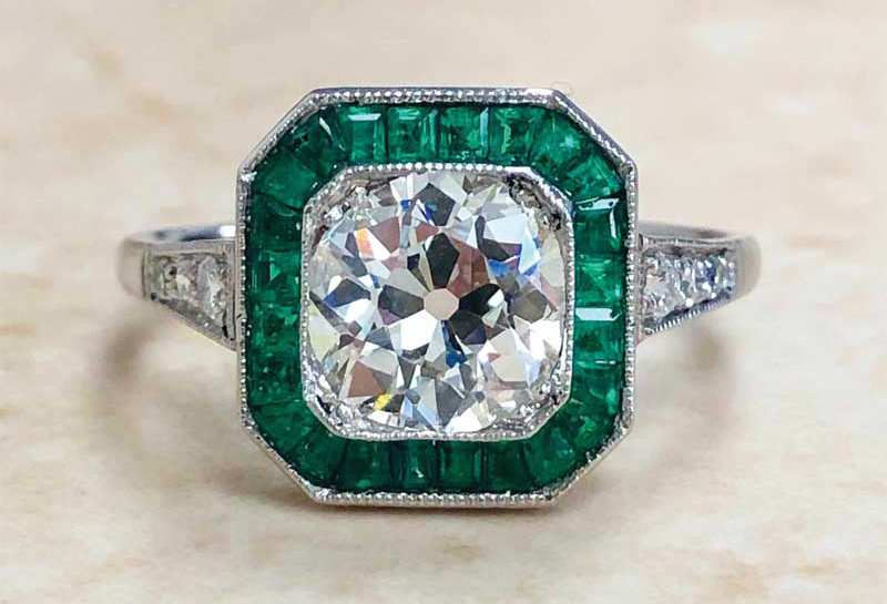 A handcrafted, platinum art deco-style diamond and sapphire halo engagement ring, featuring an emerald-cut 2.60-carat diamond centre stone (H colour, VS2 clarity).