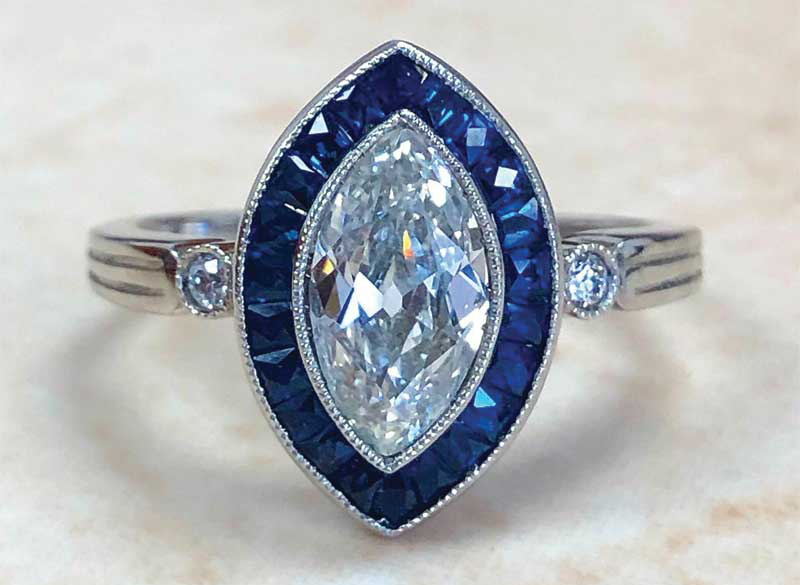 A handcrafted platinum art deco-style diamond and sapphire halo engagement ring with a 1.01-carat antique marquise diamond centre stone (H colour, VS2 clarity).