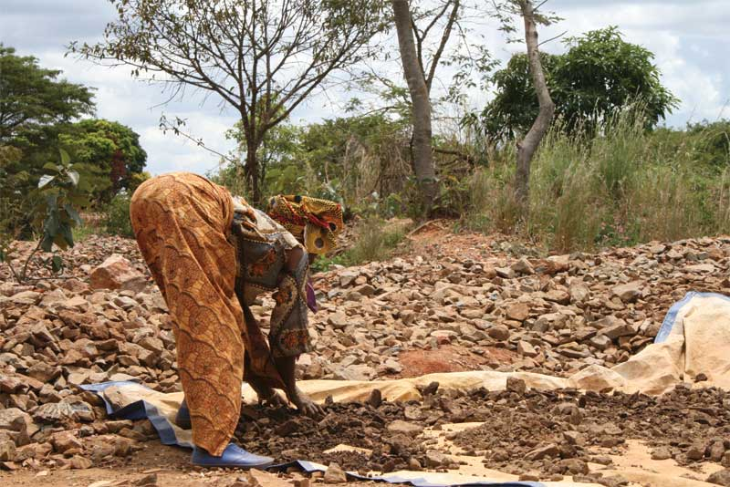 A small-scale gold miner in Kenya, breaking up dirt. About 30 per cent of small scale-gold miners are women. Photo by Marc Choyt