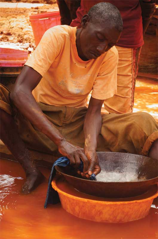A small-scale miner in Tanzania, mixing mercury with water to remove gold. Photo by Marc Choyt