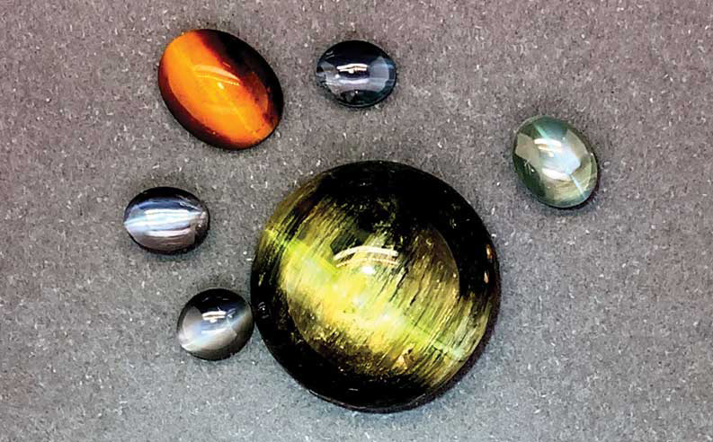 Cat's eye phenomenon showing in a green tourmaline, a tiger eye, and some chrysoberyl.